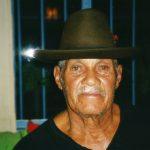 Retrato de Mané Deodato, usa chapéu e camiseta, ele está quase sorrindo.