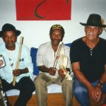 Sentados em um sofá estão Mestre Biu Roque com um reco-reco e uma lata de cerveja, Mestre Luís Paixão com uma rabeca e Mané Deodato com os braços apoiados nas pernas.