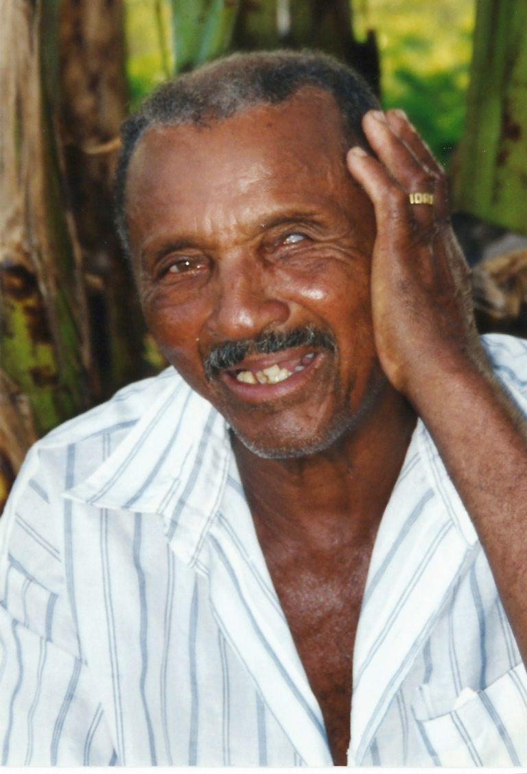Retrato de Mestre Biu Roque, sua mão esquerda está na lateral do rosto, cobrindo a orelha, ele sorri.