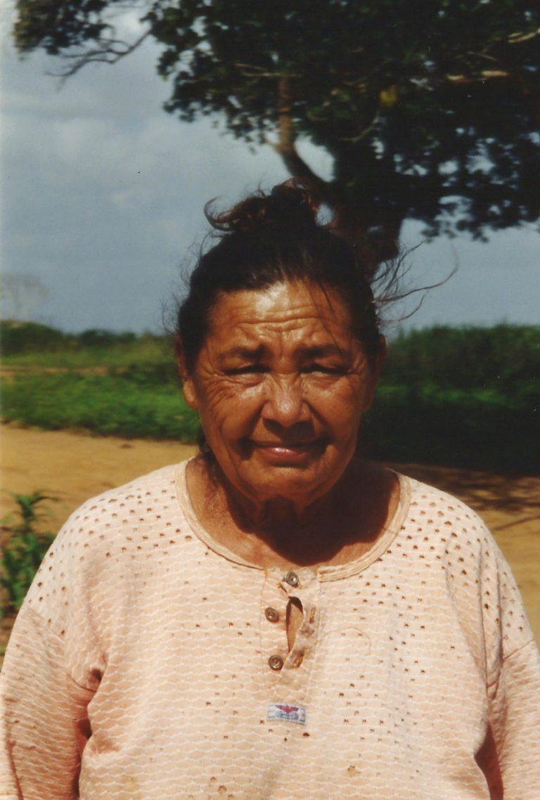 Retrato de Dona Maria, esposa de Mestre Biu Roque, de camisa e cabelo preso, ela está quase sorrindo.