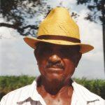 Retrato de Mestre Biu Roque, ele tem bigodes, usa chapéu e camisa social, está sério.