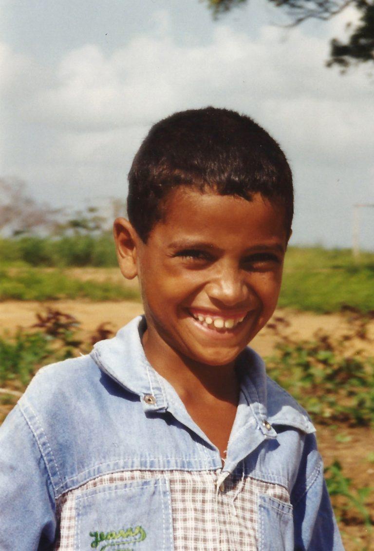 Menino de cabelo curto de camisa jeans sorrindo.