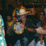 Mestre Biu Roque com um reco-reco, ao lado dele, Mané Deodato tocando pandeiro e em seguida, Mestre Luís Paixão com uma rabeca.