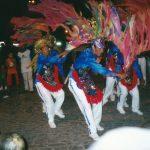 Brincantes dançam, usam calça, camisa de manga comprida e colete com bordados de lantejoulas coloridas e franja, cada um deles segura um bastão com fitas de papel, as fitas ondulam no ar.