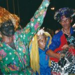 Três brincantes: do lado esquerdo há um homem com o rosto está pintado de preto, usando chapéu de fios metalizados, com o braço esquerdo levantado, no meio, um menino com chapéu de fitas de papel. Ao lado do menino, um homem de bigodes com uma burrinha.