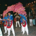 Brincantes usando calça, camisa de manga comprida e colete com bordados de lantejoulas coloridas e franja, cada um deles segura um bastão com fitas de papel, as fitas ondulam no ar.