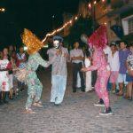 Grupo de pessoas assistindo à brincadeira: no meio estão três brincantes, um deles com máscara, calça jeans, camisa social e paletó e os outros dois vestem calça e camisa de manga comprida de mesma estampa, e chapéus de fios metalizados.