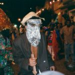 Brincante de paletó, chapéu, máscara de couro e uma espada de madeira.