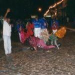 Grupo de brincantes: um homem de com o braço levantado acenando, dois de chapéu de fios metalizados estão com os braços apoiados no chão da rua de paralelepípedos, em pé atrás deles, estão quatro vestidos da mesma maneira: calça, camisa de manga comprida e colete com bordados de lantejoulas coloridas e franja.