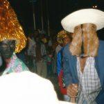 Dois brincantes: um deles usando chapéu, paletó, calça jeans, camisa social e máscara de couro, o outro usa chapéu de fios metalizados.