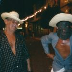 Mané Deodato de chapéu e camisa social aberta, ao lado dele, brincante com paletó aberto sem camisa por baixo, usa chapéu e máscara de couro.