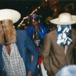 Dois brincantes usando chapéu, paletó, calça jeans e camisa social. No rosto, uma máscara de couro.