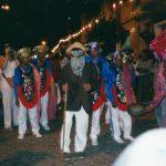 Um brincante de paletó, chapéu, máscara de couro e uma espada de madeira. Atrás dele, grupo de brincantes vestidos da mesma maneira: calça, camisa de manga comprida e colete com bordados de lantejoulas coloridas e franja.