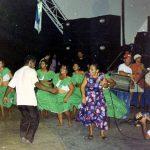 Fotografia colorida. Um grupo de seis mulheres está dançando. Elas estão vestidas com roupas de cor verde e estampa de bolinhas brancas: saias rodadas, blusa com babado sobre os ombros e umbigo à mostra. Destaque para um homem e uma mulher à frente do grupo anterior, eles aparentam estar dançando, a mulher segura um microfone. No canto direito da imagem há dois homens tocando tambores, e no canto inferior direito há um homem filmando a cena. Ao fundo, outras pessoas observam.