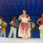 Fotografia colorida. Um grupo se apresenta em um palco. À esquerda da imagem, dois três homens tocam instrumentos percussivos. À direita, uma mulher com saia longa adornada por renda e brilho está com as mãos à cintura. Destaque para uma mulher no centro do palco, segurando um microfone na altura da boca, ela apresenta o rosto inclinado para o lado e o olhar baixo.