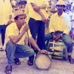 Fotografia colorida. À esquerda, um homem agachado, apoiando um instrumento de sopro em um dos joelhos flexionados, com uma mão sobre um tambor ao seu lado. Ele olha para frente. Ao seu lado, outro homem está sentado sobre um grande tambor, segurando uma baqueta para bumbo. Ao redor deles há muitas pessoas e dois homens em pé, segurando flautas semelhantes à do primeiro homem descrito.