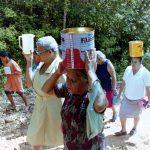 Fotografia colorida. Um grupo de mulheres caminhando em uma estrada pedregosa, margeada por arbustos. Duas delas carregam latas sobre suas cabeças, outra carrega um jarro branco erguido à altura de seu ombro. Um menino carrega uma pequena lata metálica e as acompanha.